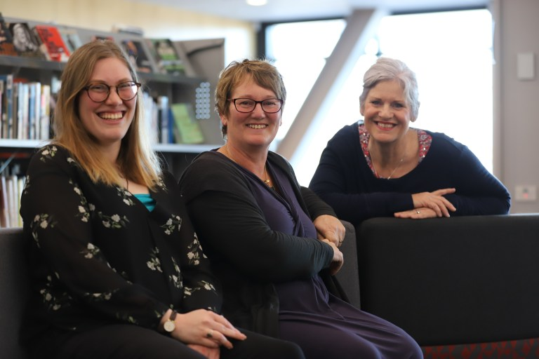 3 ladies smiling in library